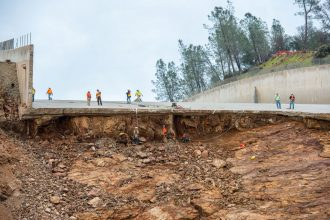 Workers assess damage following the collapse of a spillway at the 50-year-old Oroville Dam in California in 2017. FLORENCE LOW / CALIFORNIA DEPARTMENT OF WATER RESOURCES
